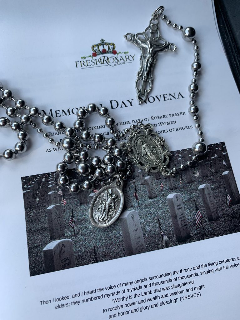 "Image of a ""Rugged Rosary"" Rosary, with center medal featuring Mary and a secondary medal featuring St. Michael the Archangel. Rosary placed on top of the Memorial Day Novena booklet by Fresh Rosary #freshrosary #freshflowerrosary #beautifulcamouflage #catholicsonline"