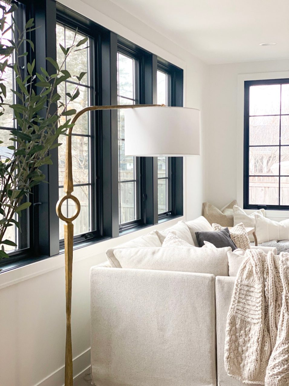 Neutral lamp and ivory couch with cream-colored blanket