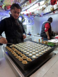 Cooking up Ebelskivers, tiny dutch pancakes, at Bucharest's Christmas Market - - Bucharest Romania - by Anika Mikkelson - Miss Maps - www.MissMaps.com