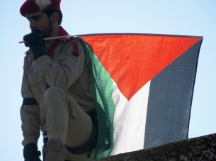 A Palestinian Soldier looks down on the crowd while holding his country's flag - by Anika Mikkelson - Miss Maps - www.MissMaps.com