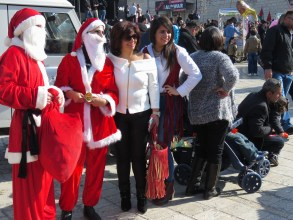 Santa Clausitas giving cookies to children and coupons to parents - Bethlehem Christmas - by Anika Mikkelson - Miss Maps - www.MissMaps.com