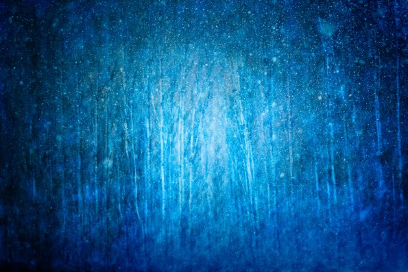 Dreamy winter abstract of blue forest through falling snow