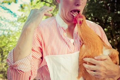 Red hen pecking at farm woman's shiny white tooth