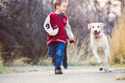 Boy and dog running together
