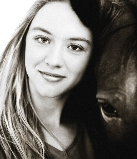 Smiling girl together with her horse