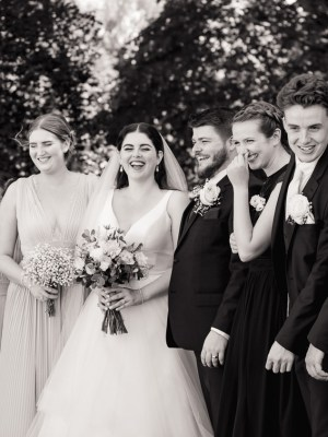 Black & white photograph of a laughing wedding group lineup