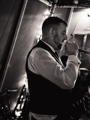 Black & white image of the groom singing