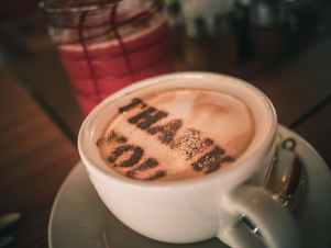 cup of aromatic cappuccino with thank you words on foam