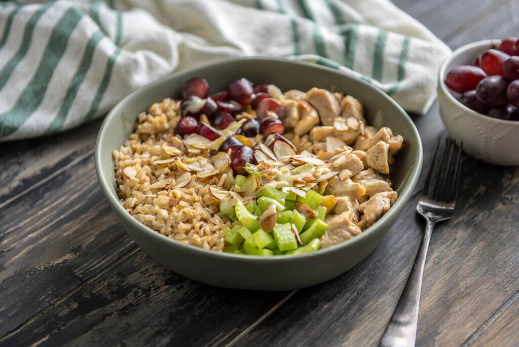 Healthy Chicken Salad Brown Rice Bowl on a wood table with a napkin, fork and bowl of grapes.