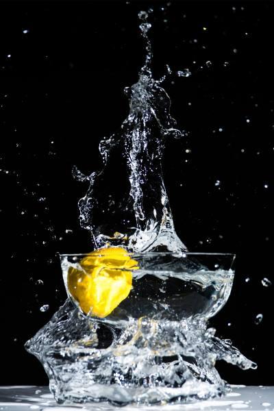 Water splashing in bowl with lemon