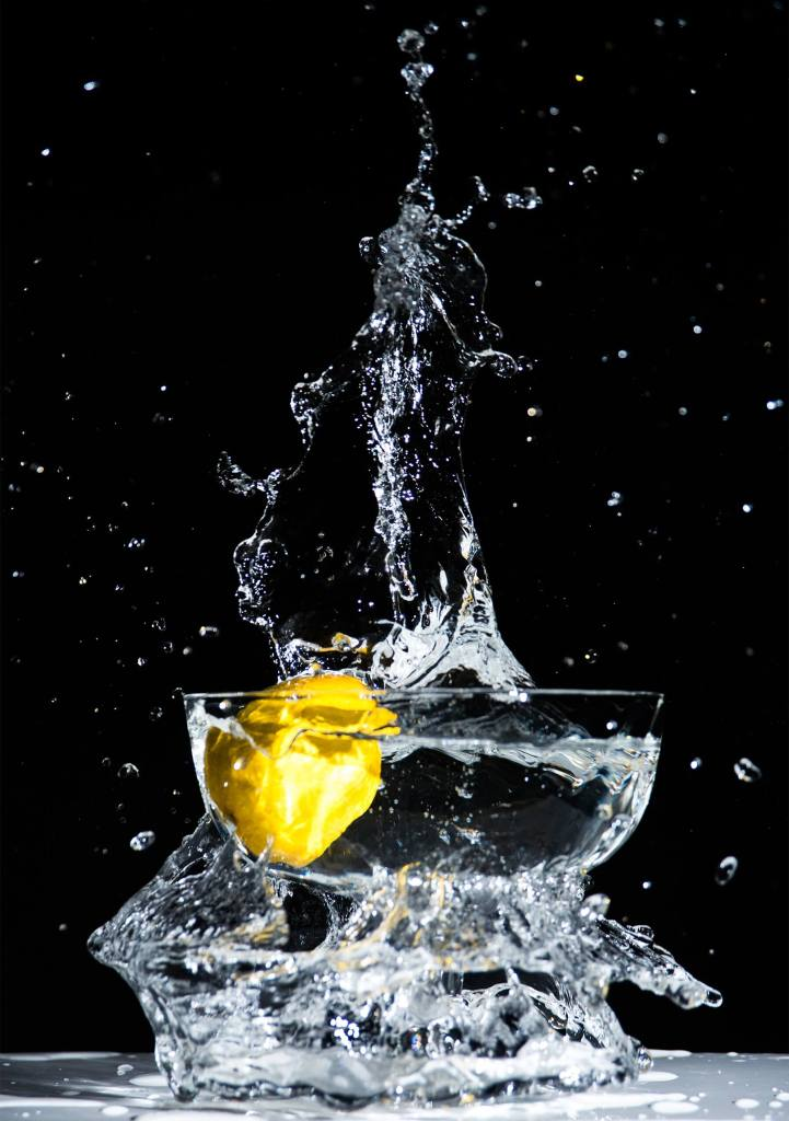 Water splashing in bowl with lemon