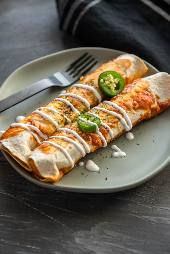 Two enchiladas on a plate with a fork