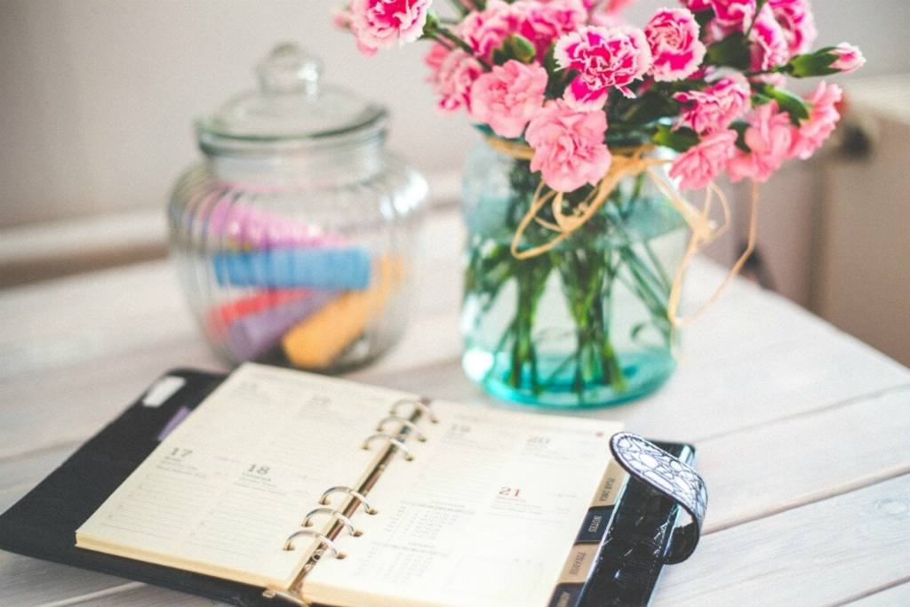 A planner, flowers and bowl on a white table
