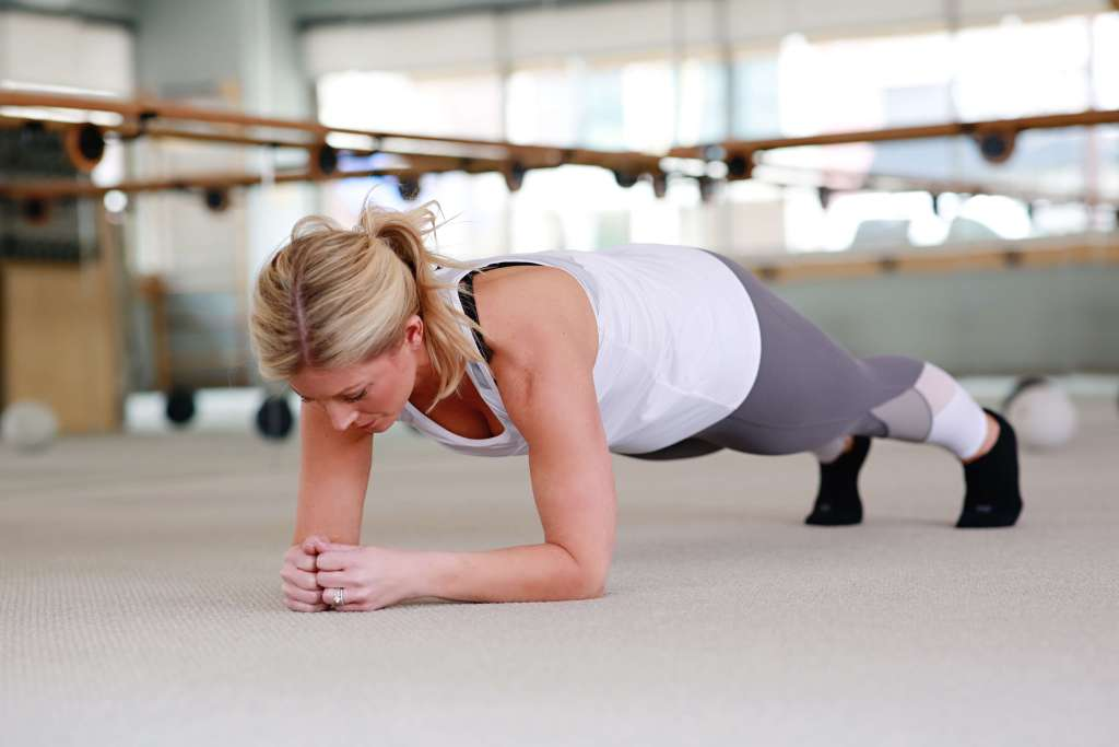 A woman with blonde hair and a white tank doing a plank at Bar Method.