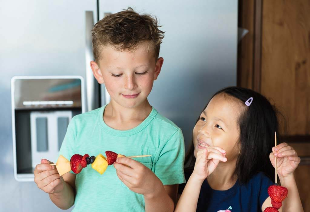 Two children smiling and making fruit kabobs