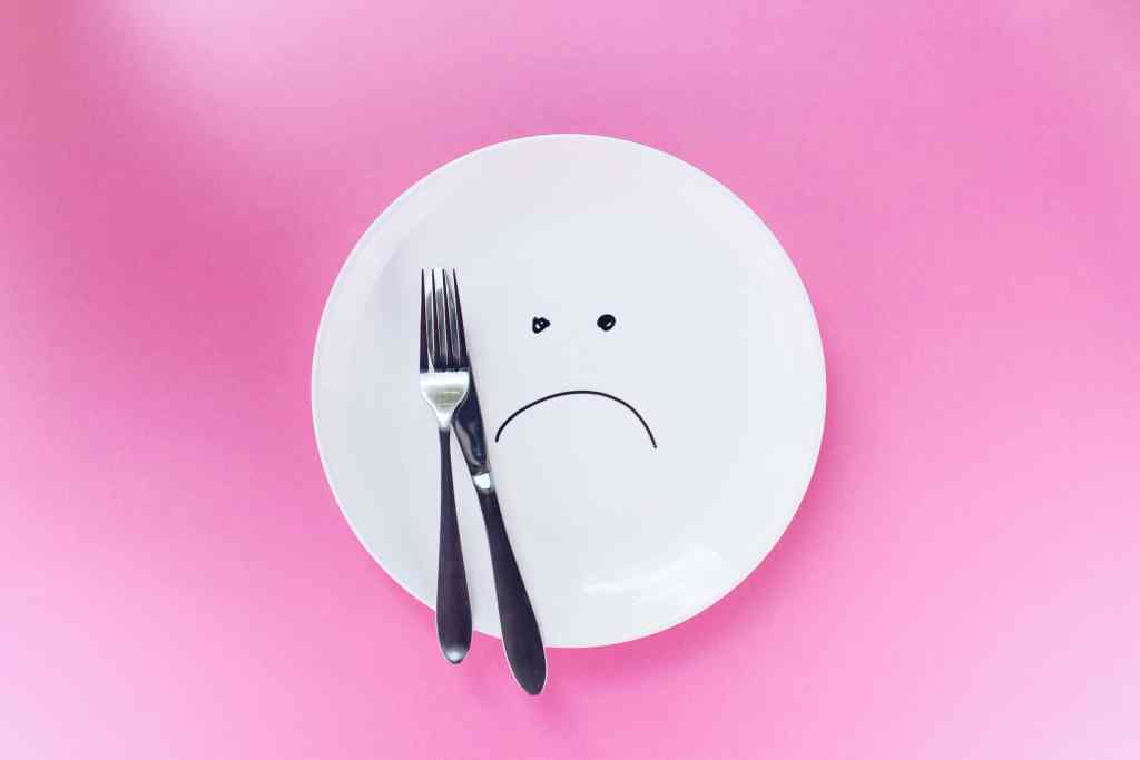 A plate with a sad face on it representing not being able to eat.