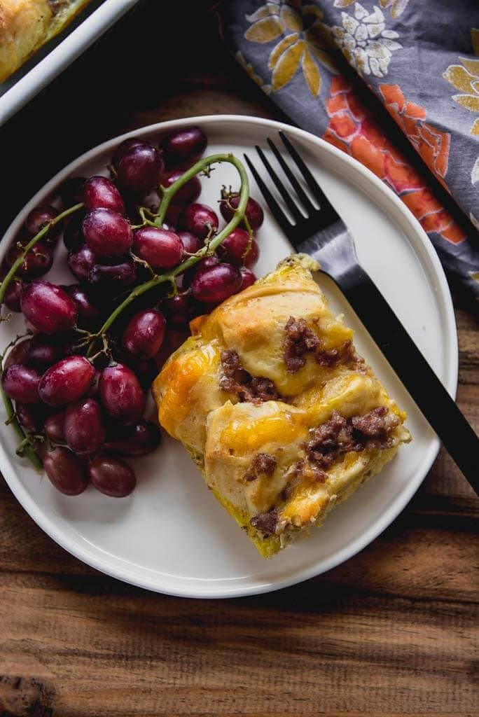 Breakfast Casserole with biscuits on a white plate with grapes