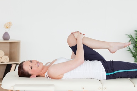 10217888 - athletic woman stretching her leg while looking at the camera
