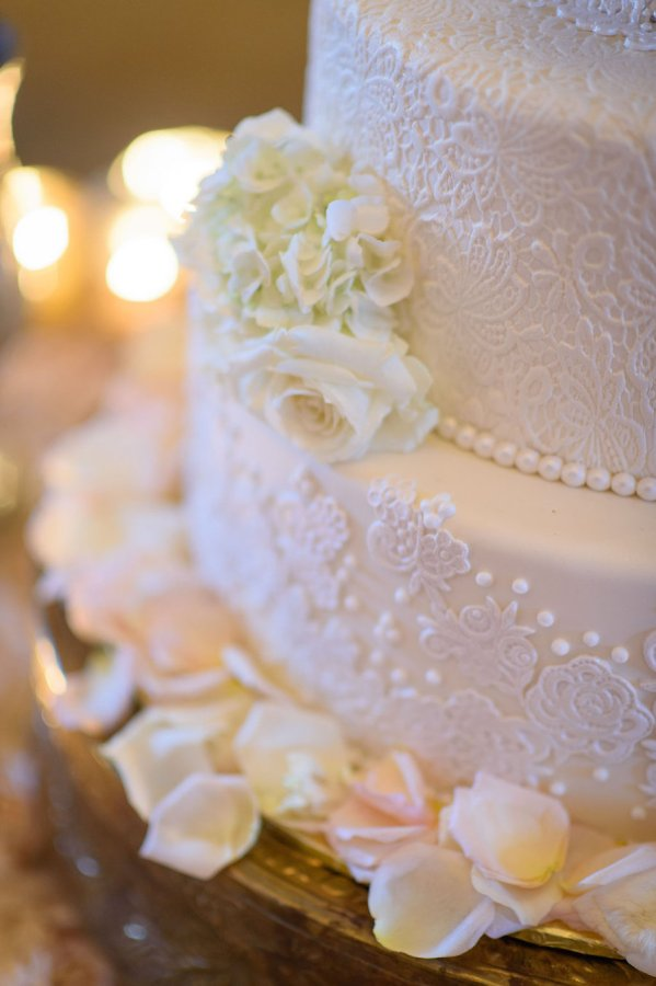 Elegant 4-Tier Round White Wedding Cake with Sugar Lace and Flower Petals