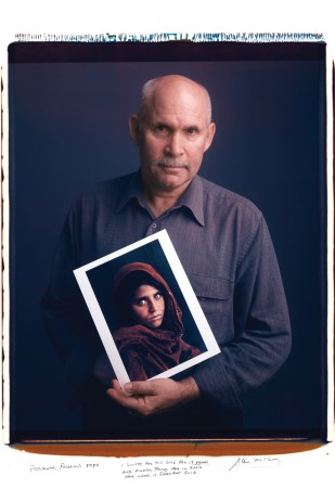 """Steve McCurry holds his 1984 photo of a young woman from Peshawar, Pakistan. """"I looked for this girl for 17 years and finally found her in 2002. Her name is Sharbat Gula."""""""