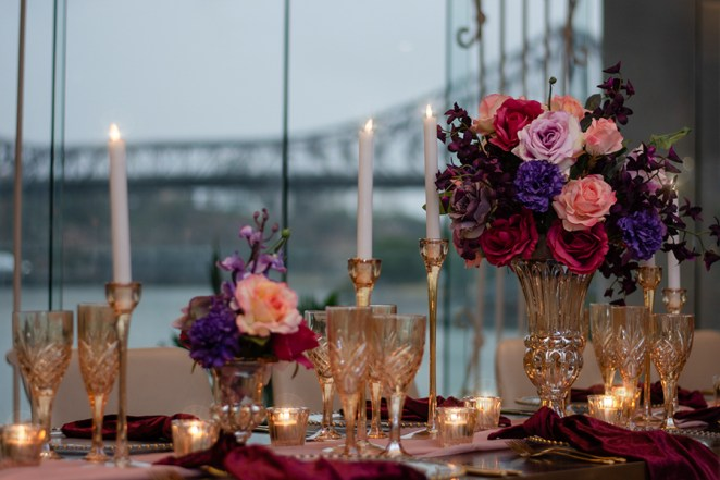 blackbird-wedding-reception-styling-amber-crystal-stemware-candlestick-holders-bright-faux-silk-flower-floral-arrangement-burbundy-velvet-napkins-blush-chiffon-table-runner-brisbane-storey-bridge-view