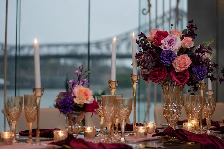 blackbird-wedding-reception-styling-amber-crystal-stemware-candlestick-holders-bright-faux-silk-flower-floral-arrangement-burbundy-velvet-napkins-blush-chiffon-table-runner-brisbane-storey-bridge-view