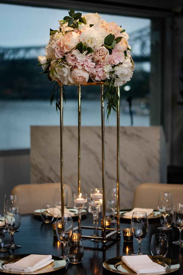 blackbird-wedding-reception-styling-gold-stand-faux-silk-blush-floral-topper-table-centrepiece-floating-candles-brisbane-storey-bridge-view