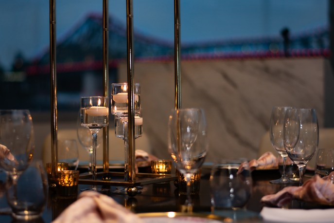 blackbird-wedding-reception-styling-gold-stand-table-centrepiece-floating-candles-brisbane-storey-bridge-view