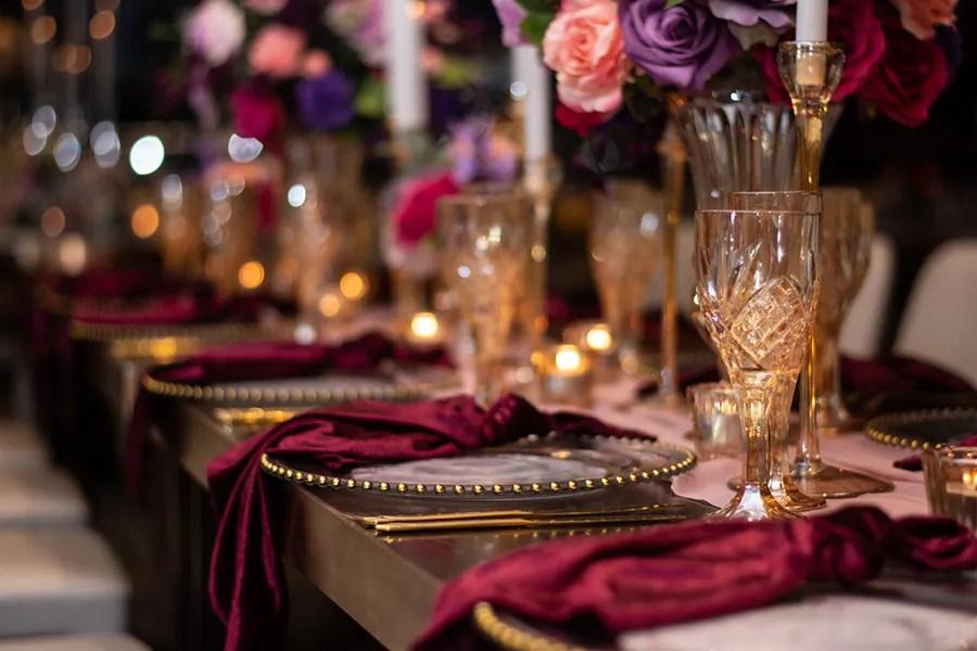 blackbird-wedding-reception-styling-amber-crystal-stemware-candlestick-holders-bright-faux-silk-flower-floral-arrangement-burbundy-velvet-napkins-gold-beaded-glass-charger-plates-blush-chiffon-table-runner