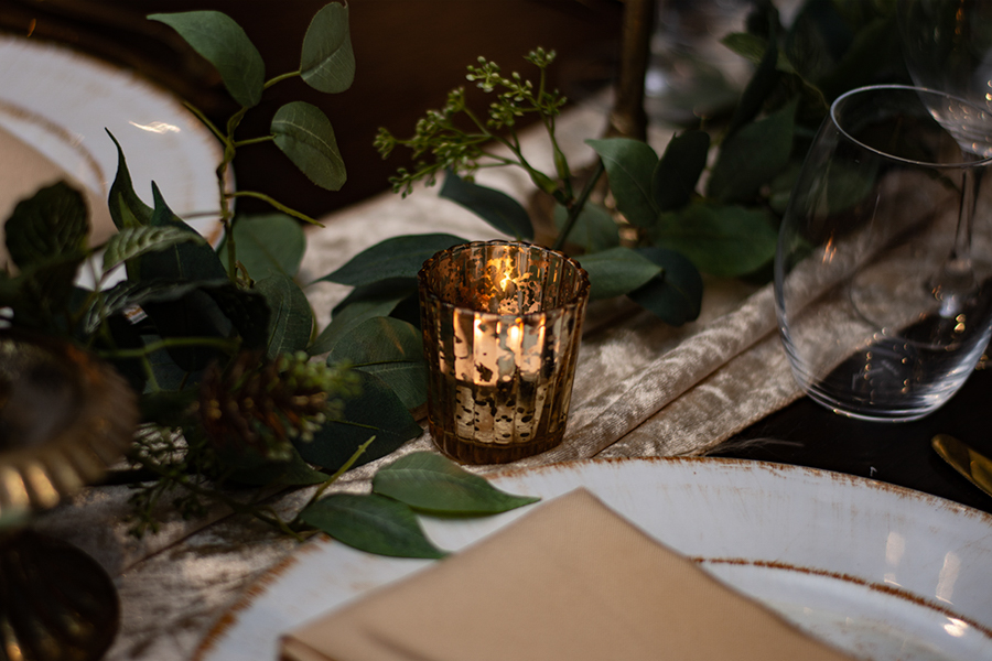 blackbird-wedding-reception-styling-champagne-velvet-table-runner-brushed-gold-candle-holders-faux-silk-greenery-linen-napkins-rustic-charger-plates