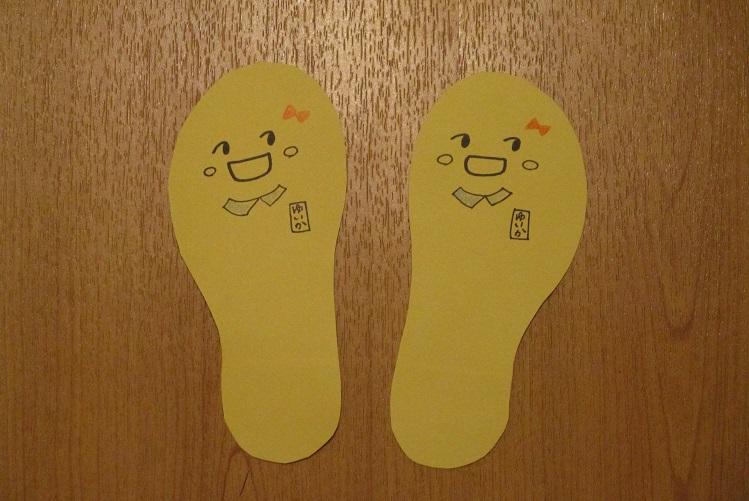 子供が靴を揃える足形顔を描く