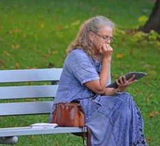 women on park bench reading
