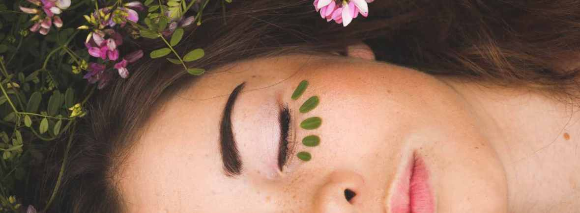 Beautiful, relaxed woman laying down surrounded by grass and wild flowers. Small leaves placed under eye.