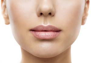 A woman's plump, luscious, full lips showing benefits of lip fillers. Hydrated, wrinkle free skin.