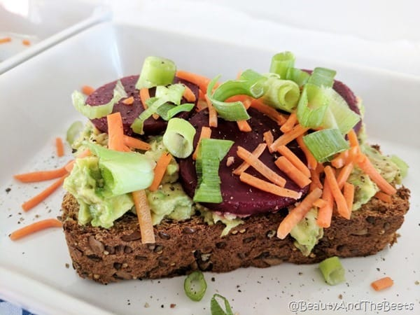 A slice of bread with mashed avocado, grated carrots, sliced red beets and green onions on a square plate