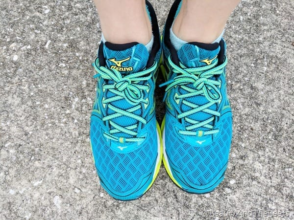 A pair of blue, aqua and yellow shoes from Mizuno on pavement