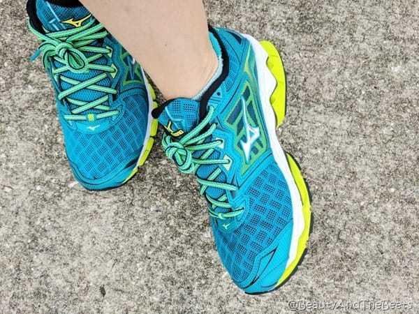 Crisscrossed feet wearing a pair of Mizuno blue, aqua and yellow shoes on pavement