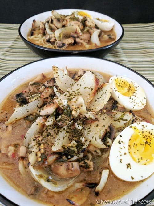 a bowl of noodle soup with onions and soft boiled eggs in a white bowl on a green striped placemat