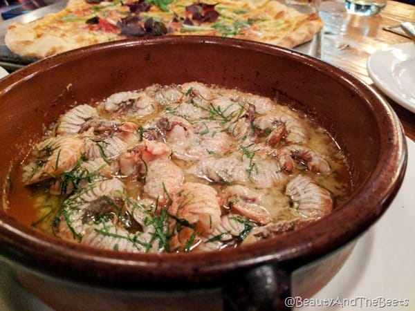 A brown bowl of rock shrimp in garlicky butter