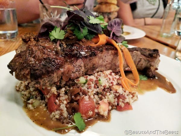 A large steak on a bed of red and white quinoa and tomatoes with juices on a white plate