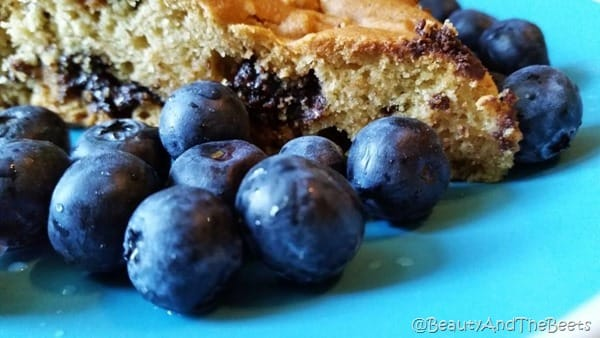 a slice of Vegan chocolate chip breakfast cake surrounded by bright blueberries on a blue plate