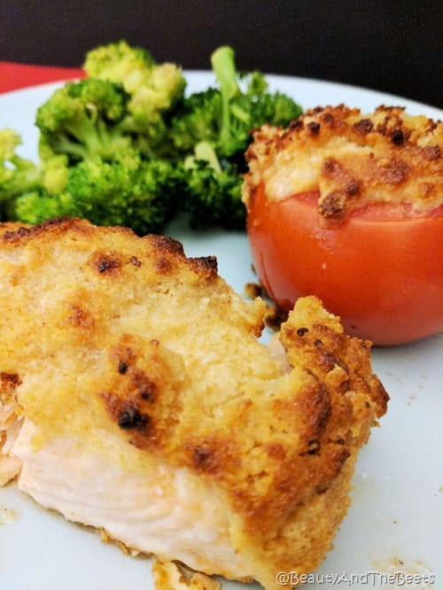 a pitcure of salmon with a golden mayo crust with a crusted tomato and a small portion of green broccoli on a blue plate with a black background