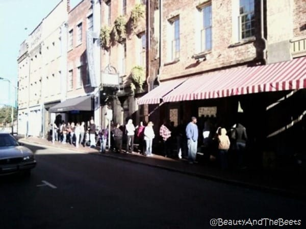 a line of people at LAdy and Sons a red brick building on a block of historic buildings