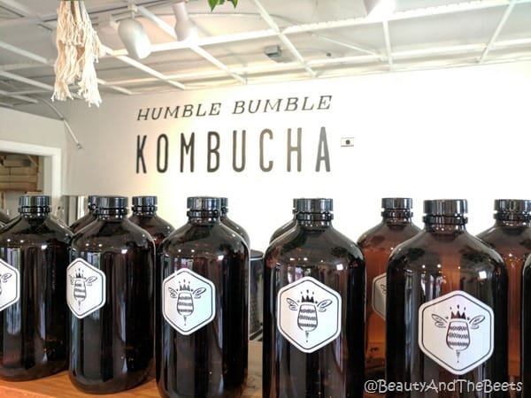 a row of brown growlers on a shelf with a white wall in the background