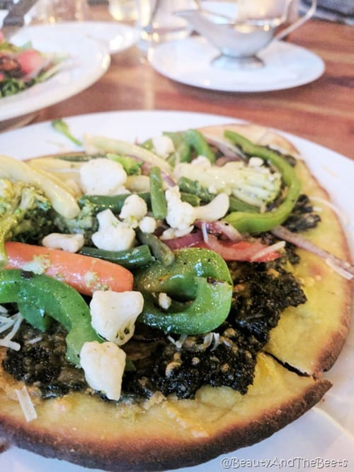 A round flatbread pizza topped with green peppers, carrots, cauliflower and pesto on a white plate and a wooden table