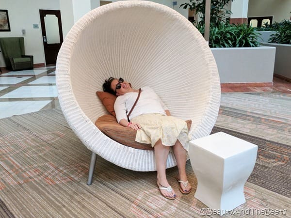 picture of the author wearing a yellow skirt and a white sweater in a white wicker pod chair