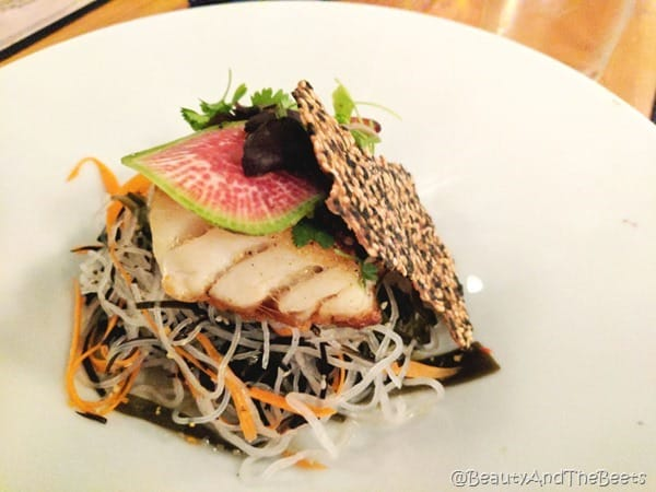 A slice of red snapper fish on a bed of cellophane noodles and seaweed salad on a white plate