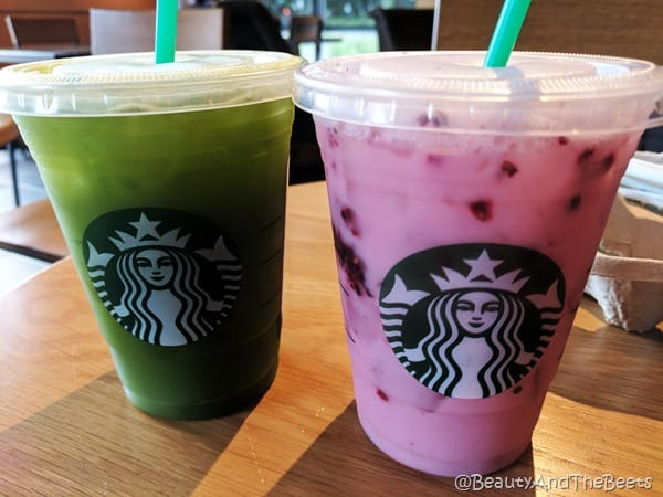 A pink Starbucks drink and a green Starbucks drink togather on a wooden table