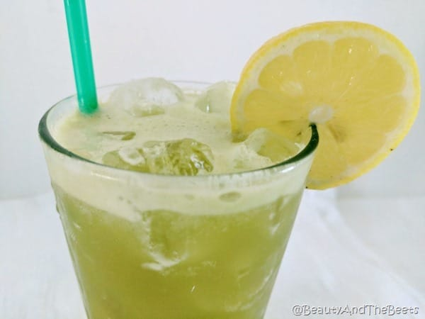 a glass of green matcha lemonade over ice with a green straw and a lemon slice on a white background