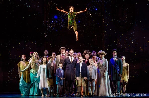 The Cast of FInding Neverland on a stage with Peter Pan flying over them with a stars background
